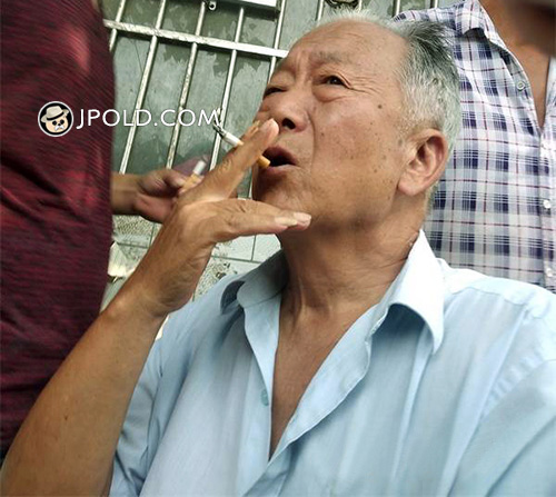 Old man in white shirt smoked in the street