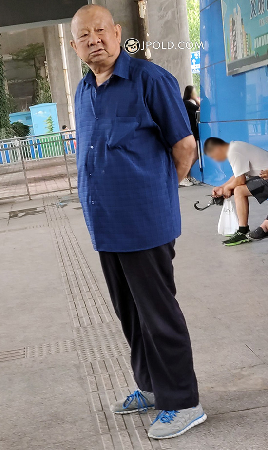 Bald head grandpa in blue shirt and black trousers stood in the passage
