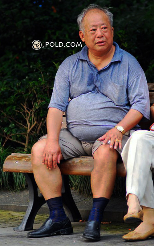 Fat old daddy rest on the bench in the park