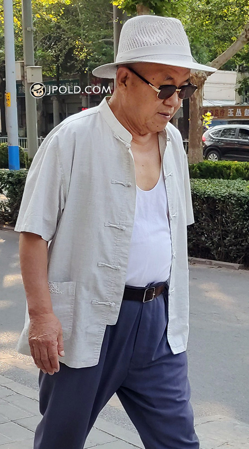 Old man in white vest shirt and blue trousers walked in the street