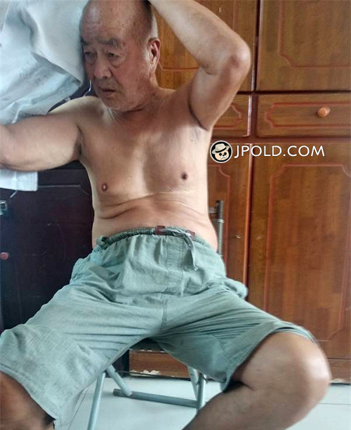 Old daddy in a grey trousers in the bedroom