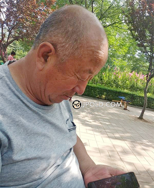Old daddy was playing cellphone game in the park