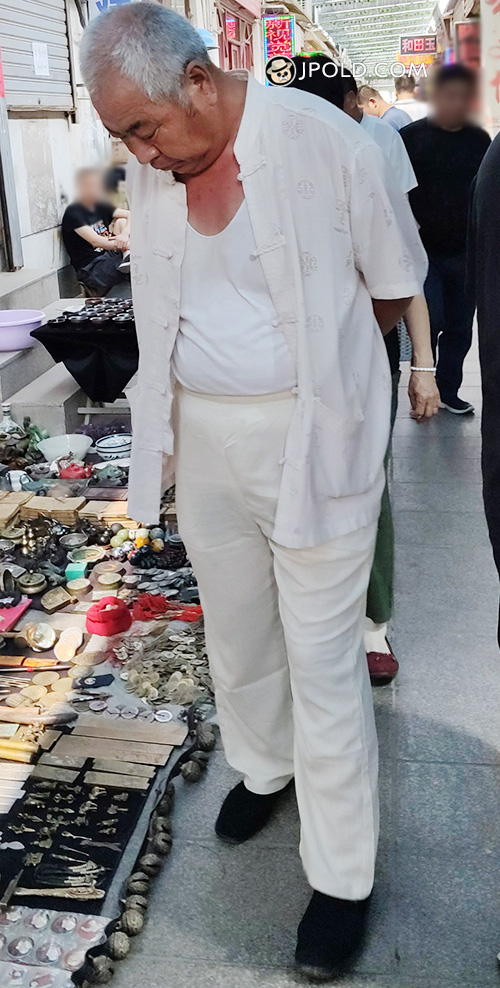 White hair old man in white clothes in the street market