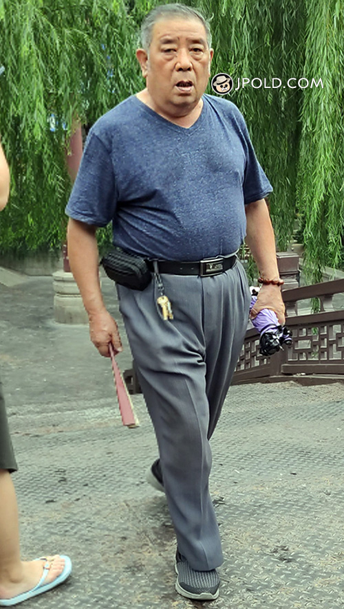 Old man in brown T-shirt and blue trouser walked