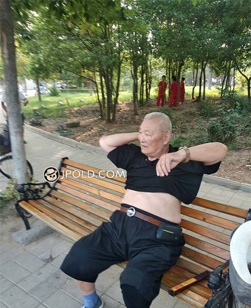 Fat old man took off his black T-shirt on the bench