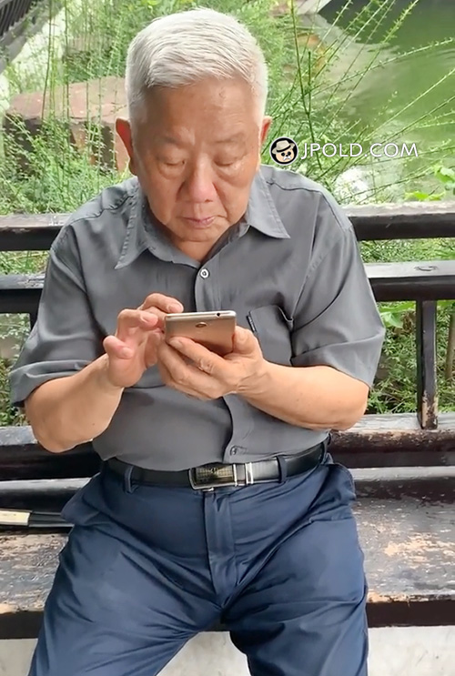 White hair old man in blue trousers played cellphone