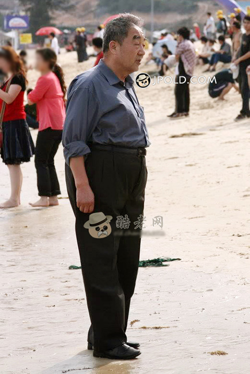 Old man in brown shirt stood on the beach