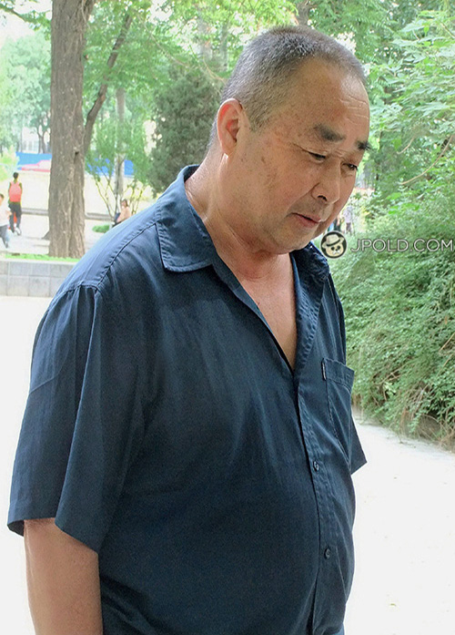 Blue shirt old daddy watched people played Chinese chess