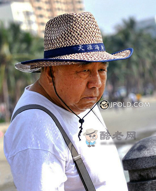 Fat old man wore a hat stood by the beach