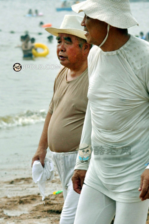 Two tourists old men walked on the beach