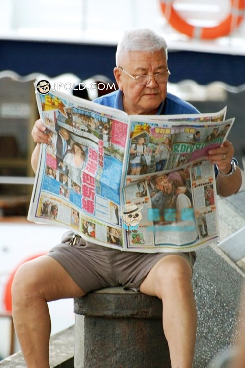 White hair old man in blue polo shirt read newspaper
