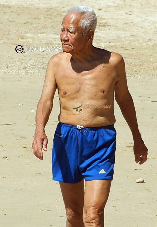 White hair old man in a blue boxer pants walked on the beach