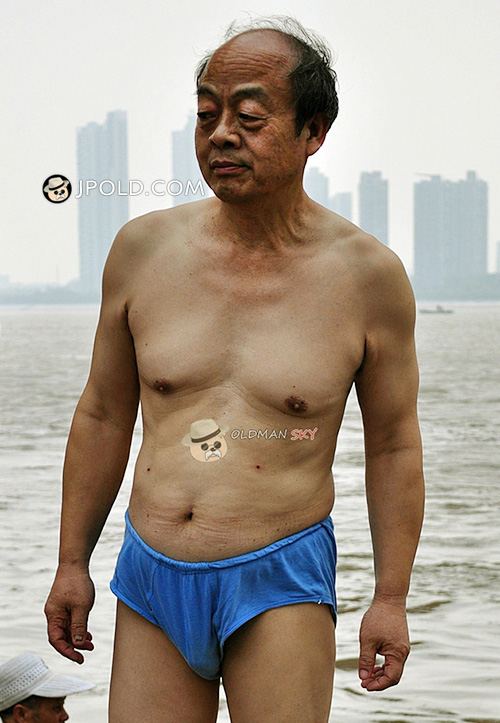 Old man in a blue underwear at the sea
