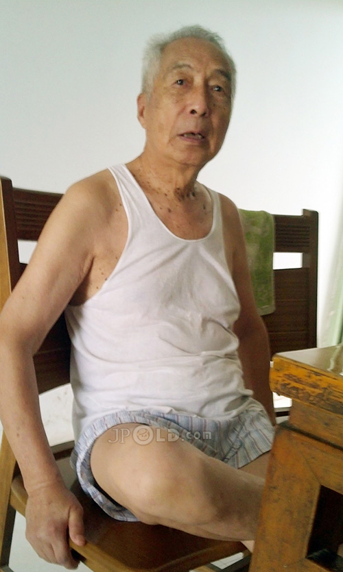 Old man in white vest undershirt and underwear at home