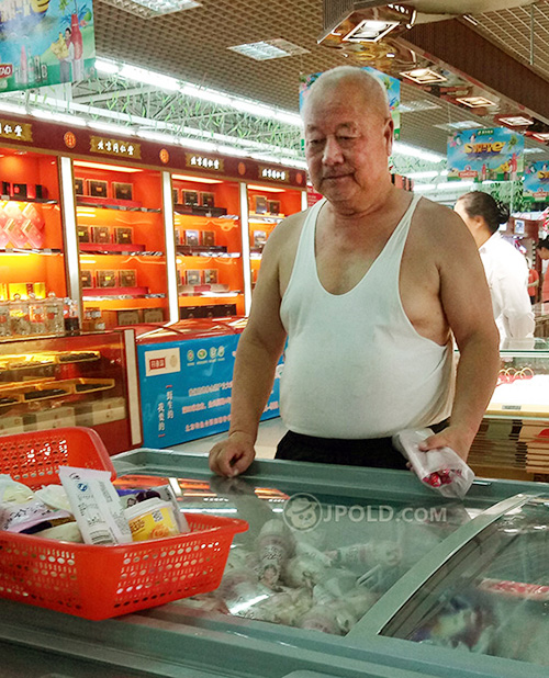 Old man in white vest undershirt shopped in the market