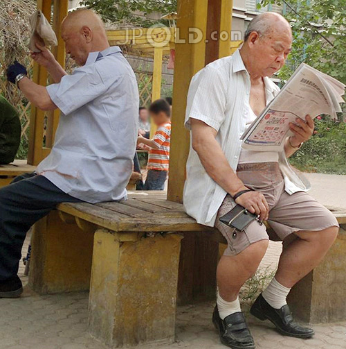 Old man was reading newspapers in the bower