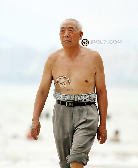 Tourist old man in a grey trousers walked on the beach