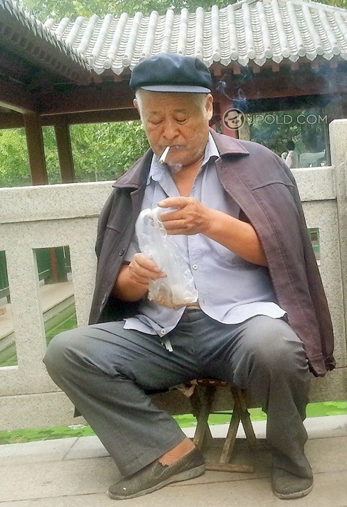 Old man in grey clothes smoke in the park
