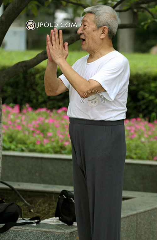 Old man in white undershirt and grey trousers played TaiChi