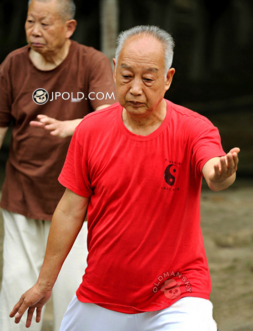 Old man in red T-shirt and white trousers played TaiChi