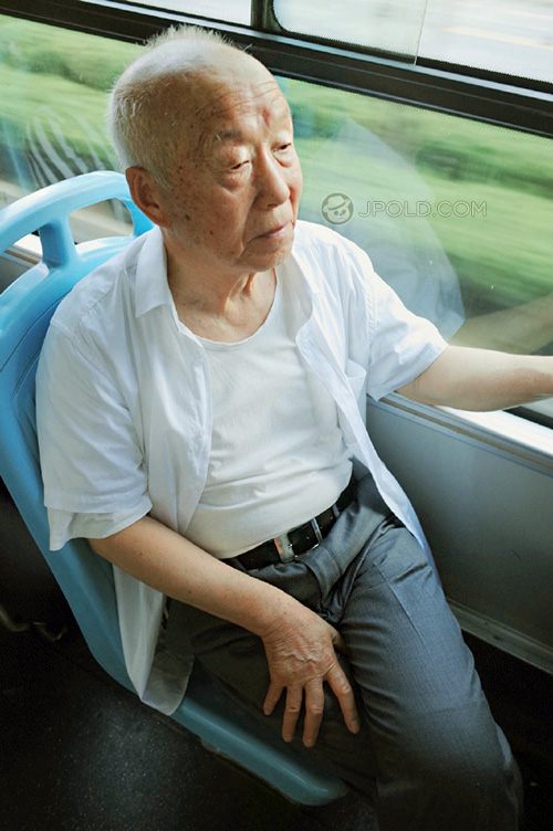 Old man in white shirt and blue trousers by bus