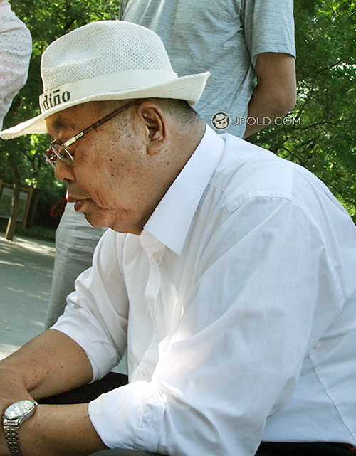 Glasses old man in white shirt and wore a white hat played Chinese chess
