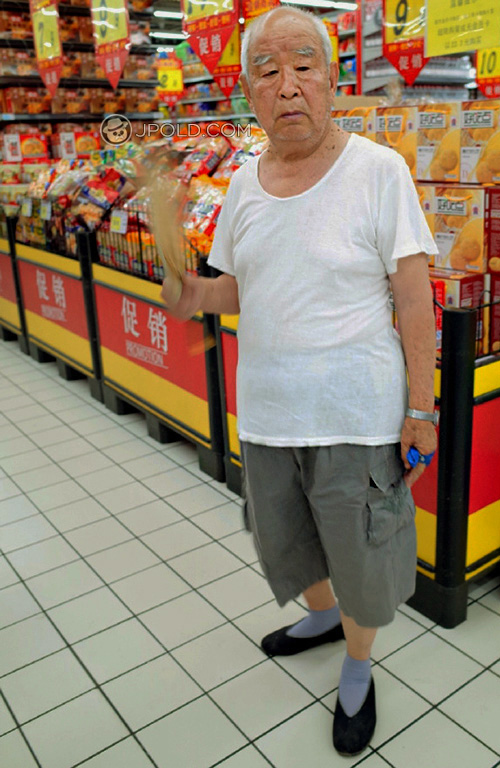 Old man in white undershirt and grey middle pants in the supermarket