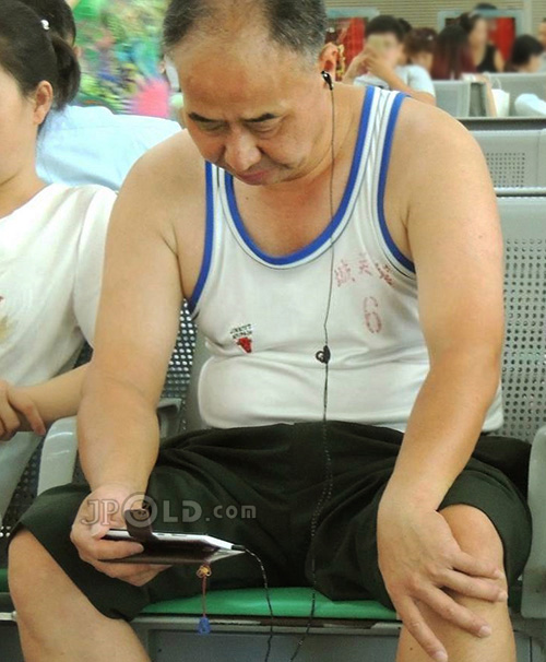 Old daddy in white vest undershirt played cellphone in the railway station