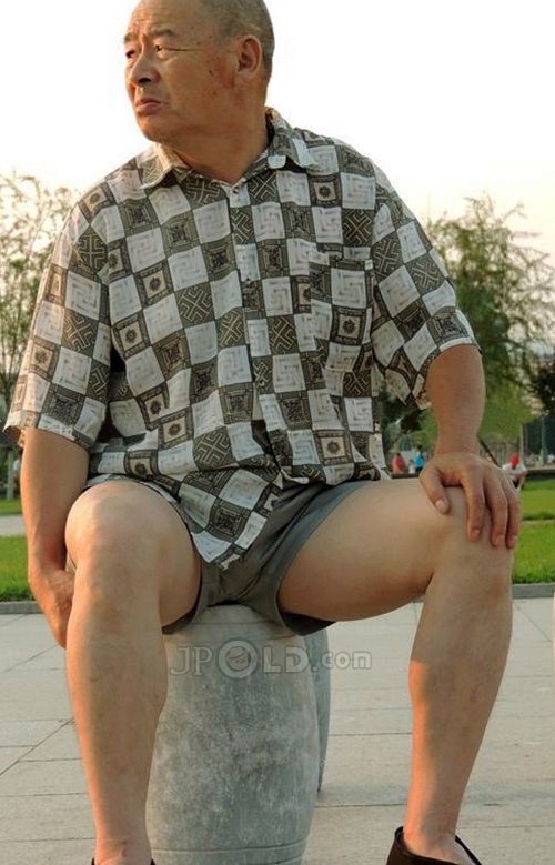 Old man in plaid shirt and middle pant sat in the park