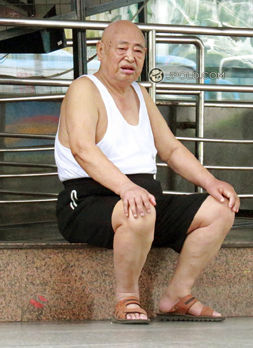 Old man in white undershirt and black middle pants sat by the roadside