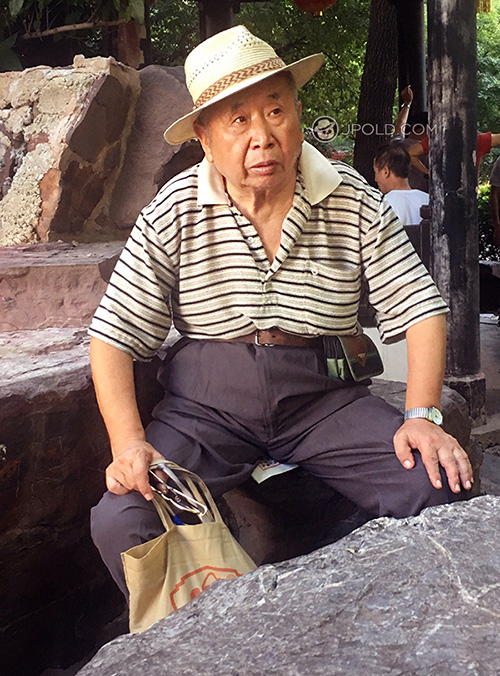 Old man wore a hat rest on the stone bench