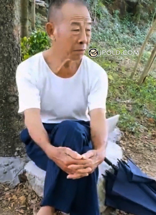 Old man in white T-shirt and brown trousers sat on a rock