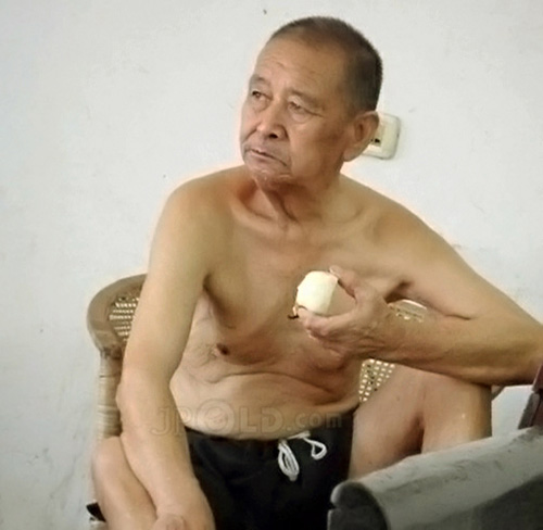 Old man in a black middle pants ate pear at home