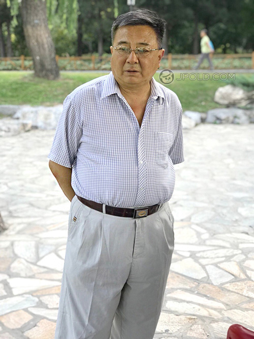 Glasses old daddy in white clothes stood in the park