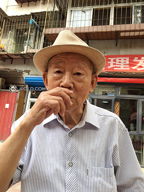 Old man wore a hat talked in the street