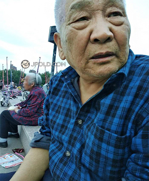 White hair old man in blue plaid shirt rest on the square
