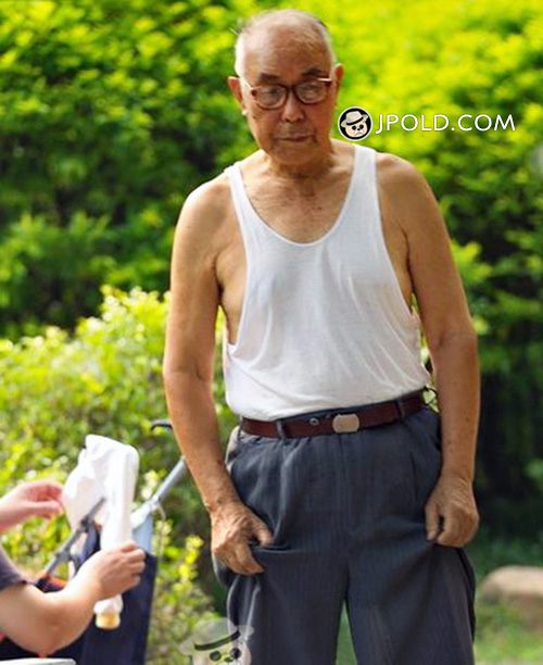 Glasses old man in white vest undershirt and blue trousers