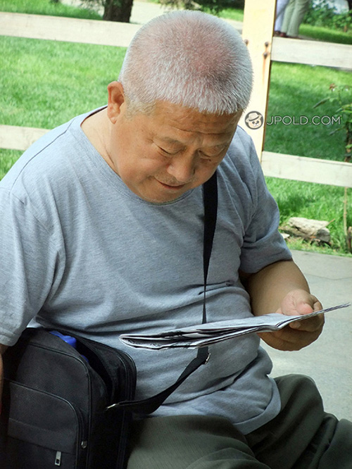 Fat white hair old daddy read newspaper in the park