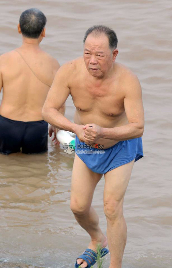 Father in blue underwear swimming in river