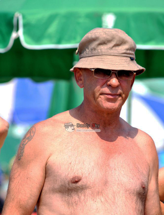 Sexy daddy in a hat on beach