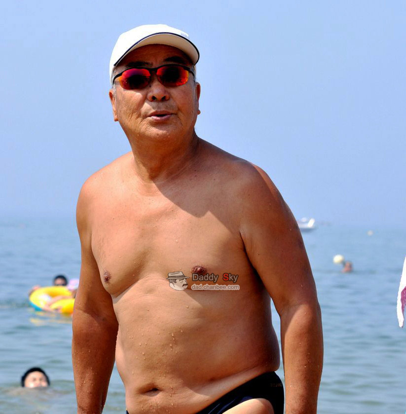 Swimming daddy in a cap on the beach