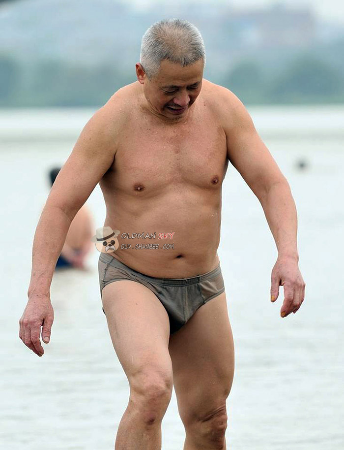 Swimming old man in a black underwear stood on the beach