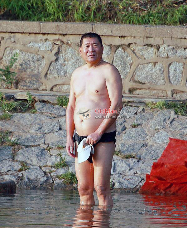 Swimming uncle wiping his body on the lake