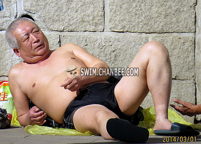 Chubby swimming old man in black underwear lying on the ground