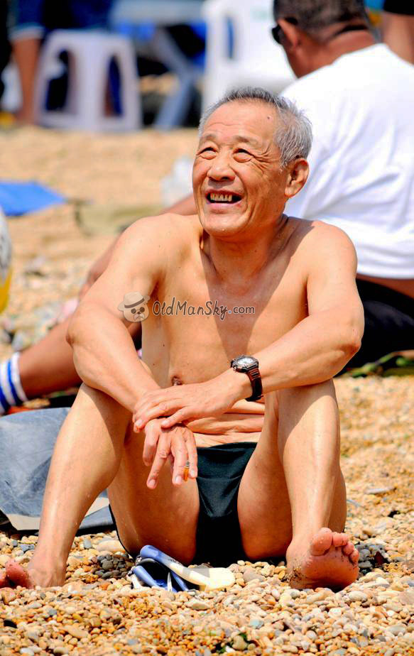 Old man in a black underwear sitting on the beach