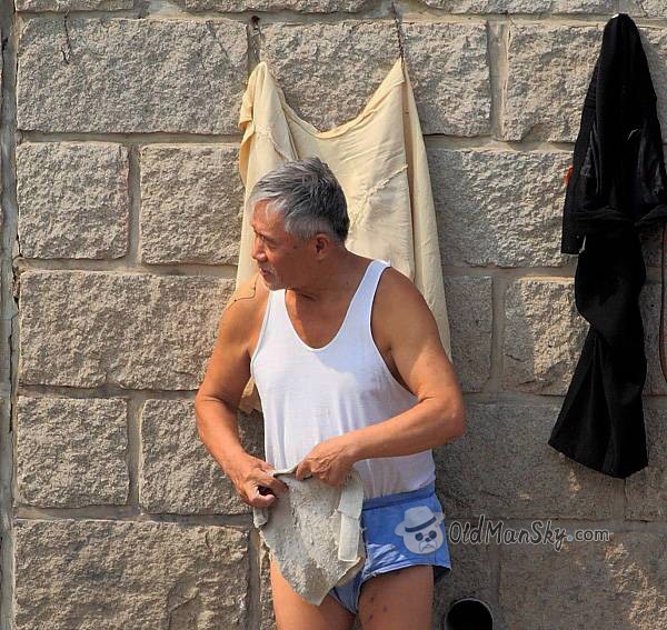 Swimming old man in blue underwear and white vest