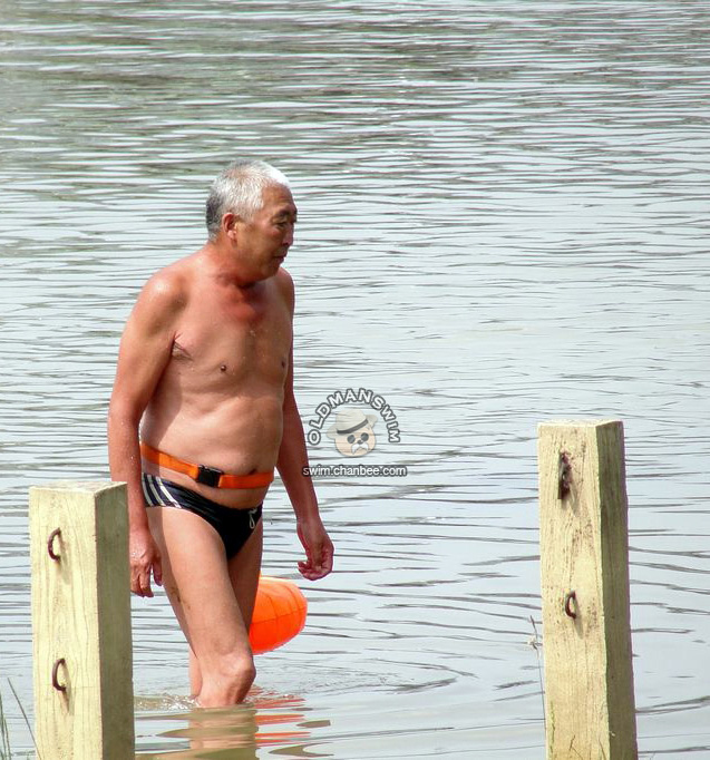 Belly white hair old man in a black underwear out of lake
