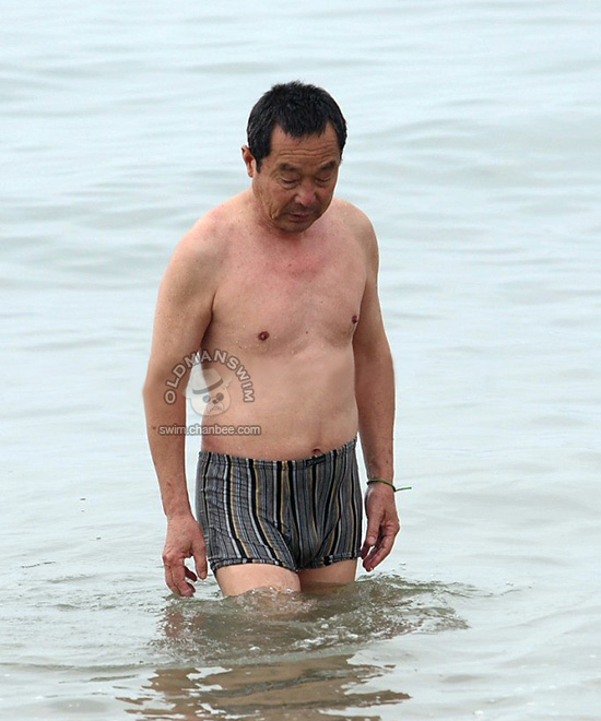 Swimming old man in a striped pants out of water
