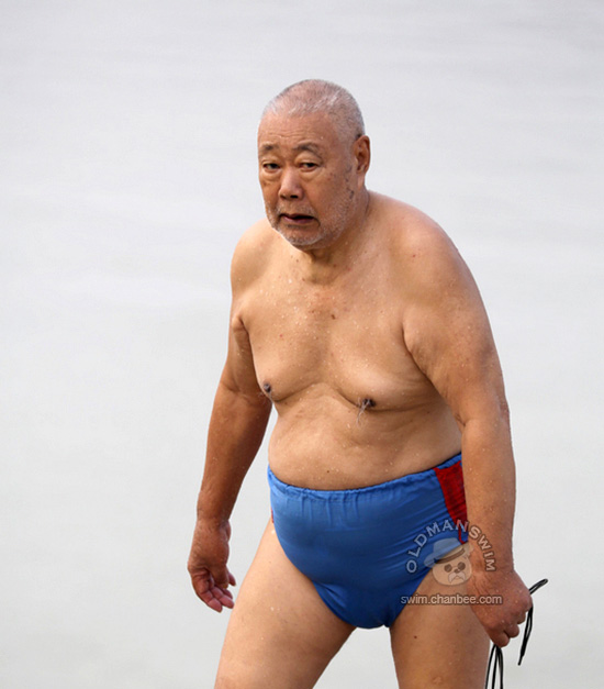 Fat swimming old man in a blue swimsuit underwear out of water