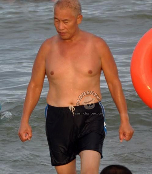 Swimming old man in a black Mid-pants out of water